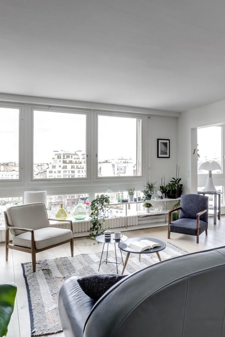 Esempi arredamento soggiorno con tavolini rotondi, divano di pelle e tante piante da appartamento