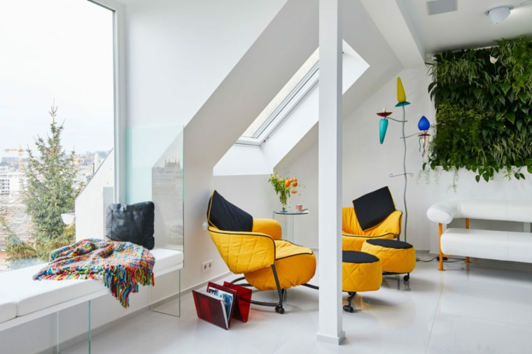 Soggiorno con soffitto in pendenza di colore bianco e arredamento con poltrone gialle
