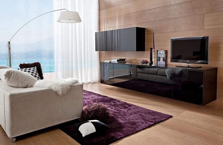 Arredamento moderno per il soggiorno con un mobile nero lucido sospeso e divano bianco di tessuto