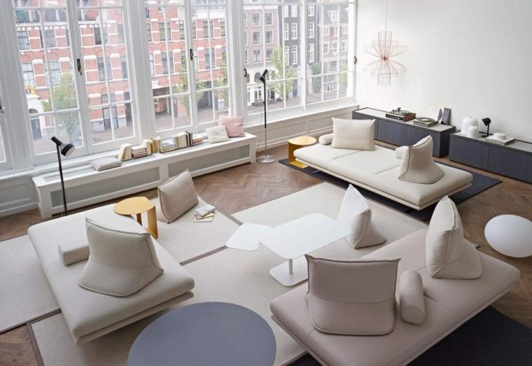 Salotto arredato con mobili moderni di colore bianco, parete bianca con un lampadario di metallo a sospensione