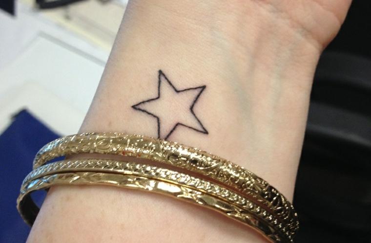 Simbologia tatuaggi e un'idea con il disegno di una stella sul polso della mano di una donna