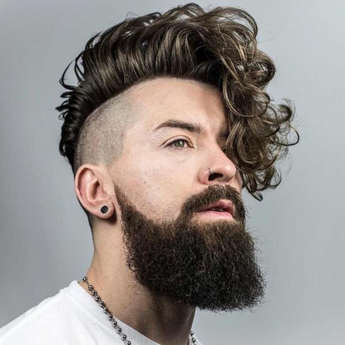 Piega capelli mossi di un uomo rasato ai lati, viso di profilo con una barba lunghissima