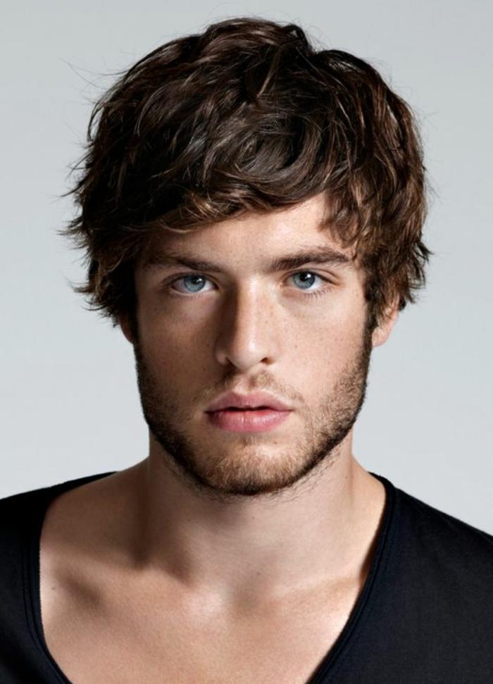 Un ragazzo con gli occhi azzurri e i capelli ricci di colore castano con pettinatura mossa