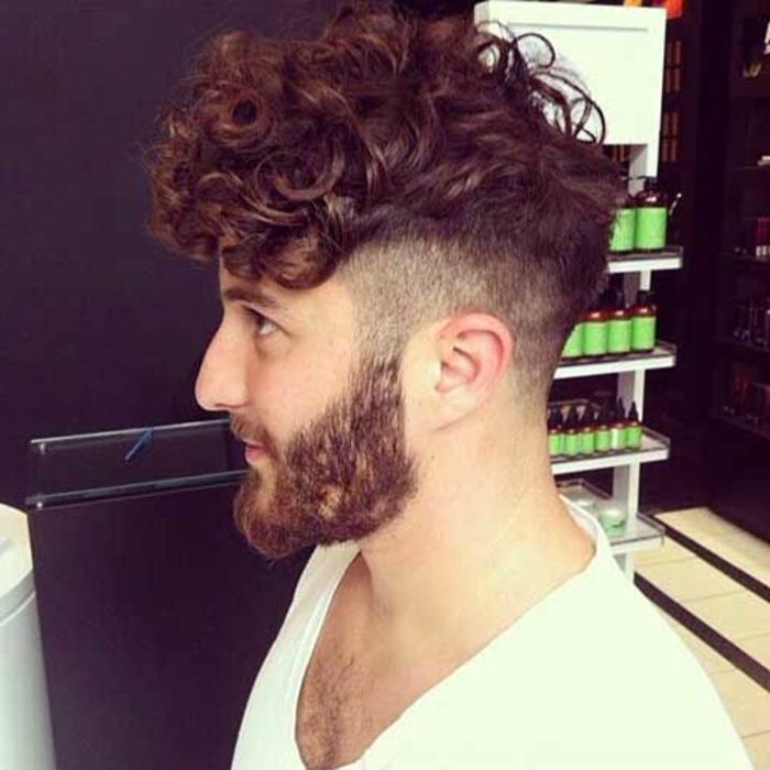 Acconciature capelli corti ricci di un uomo rasato ai lati della testa