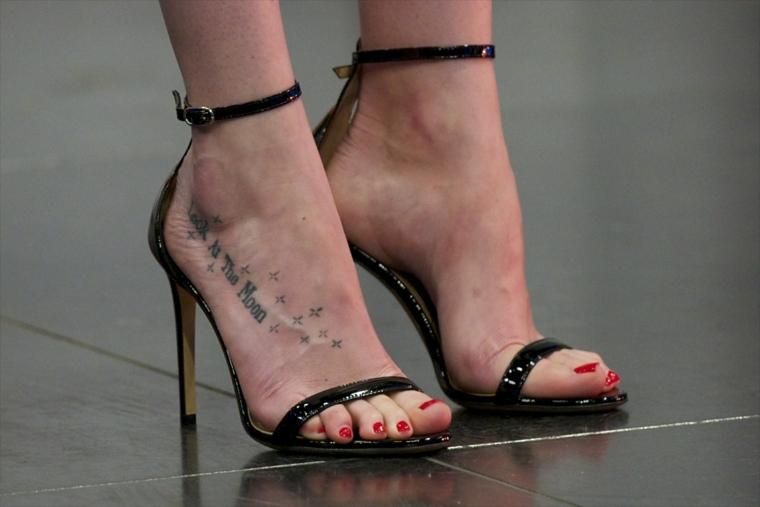 Tattoo particolari e un'idea per tatuaggio con scritta e stelle sulla gamba di una donna con i tacchi alti