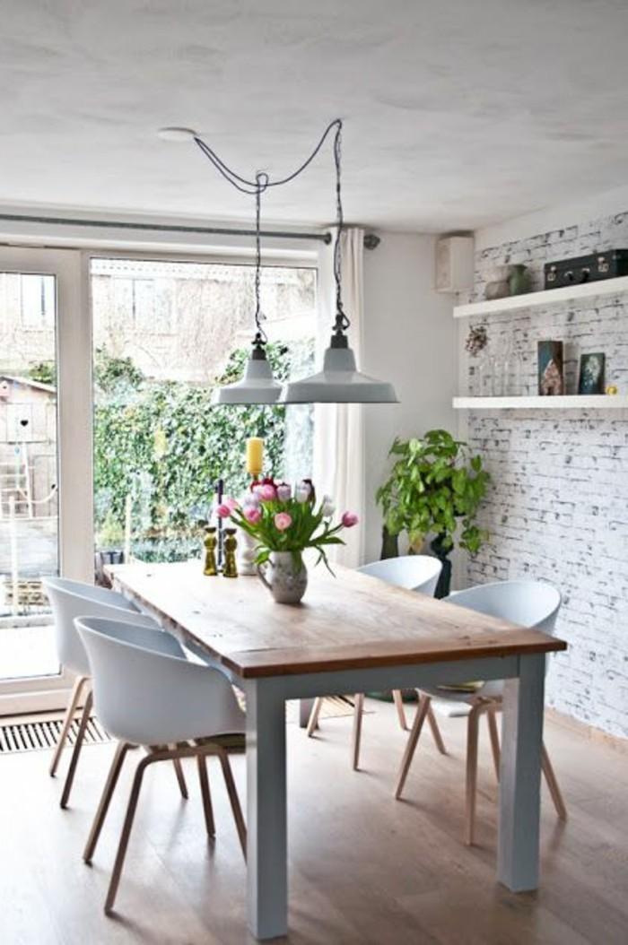 Parete con mattoni a vista di colore bianco e un tavolo di legno con sedie bianche