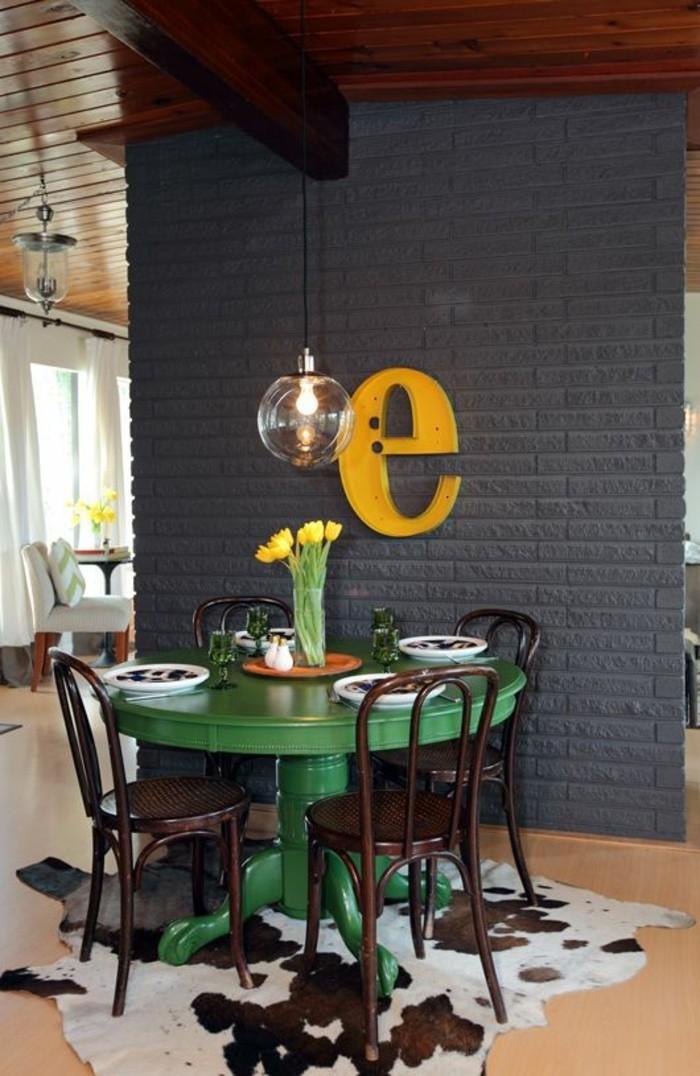 Piccola sala da pranzo con un tavolo verde rotondo e sedie, decorazione da parete con una lettera gialla