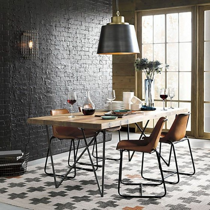 Parete con mattoni a vista di colore nero e un tavolo da pranzo di legno