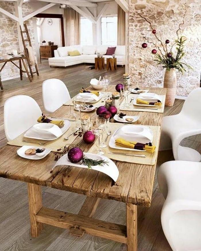 Sala da pranzo con un tavolo decorato con palline viola natalizie