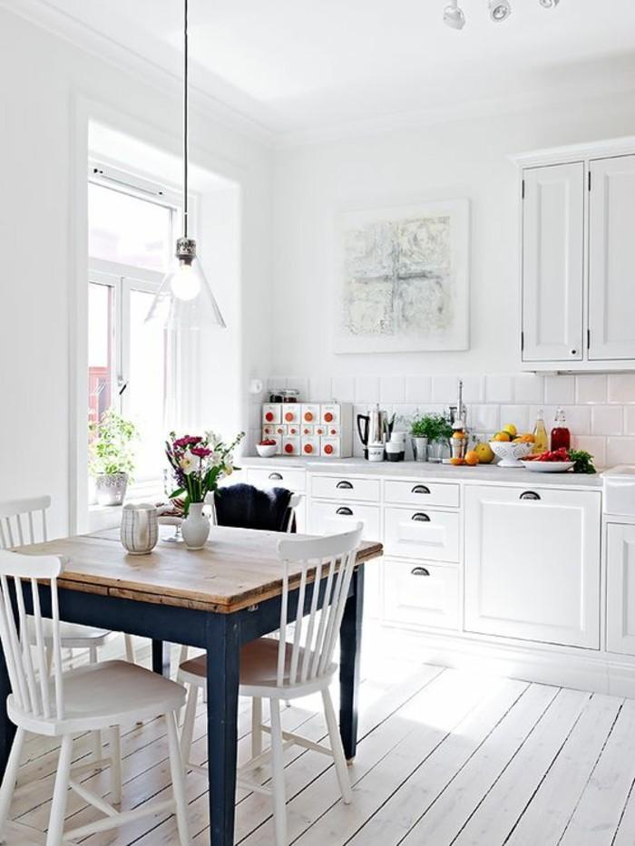 Arredamento cucina con mobili di colore bianco e un tavolo da pranzo rustico con sedie bianche