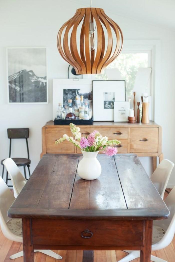 Arredare la sala da pranzo con un tavolo di legno, decorare con un lampadario a sospensione