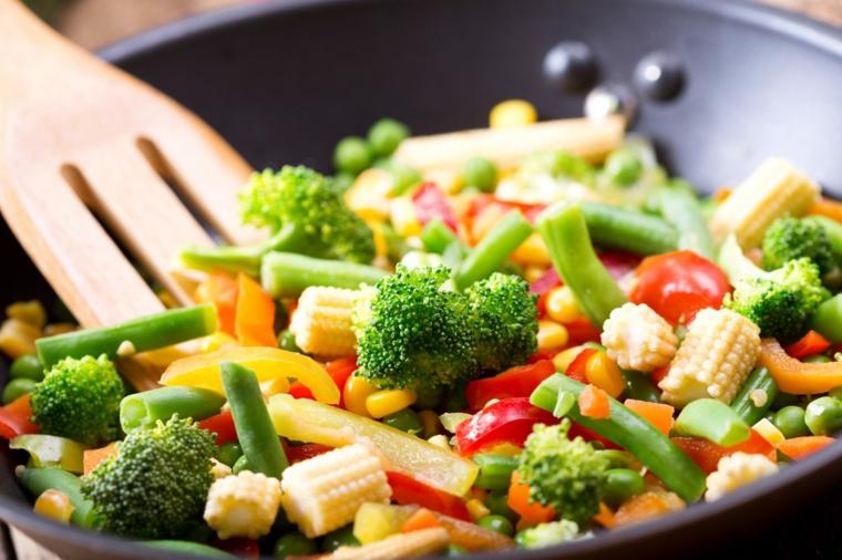 Dieta senza carboidrati e zuccheri, verdure miste in padella con un mestolo di legno