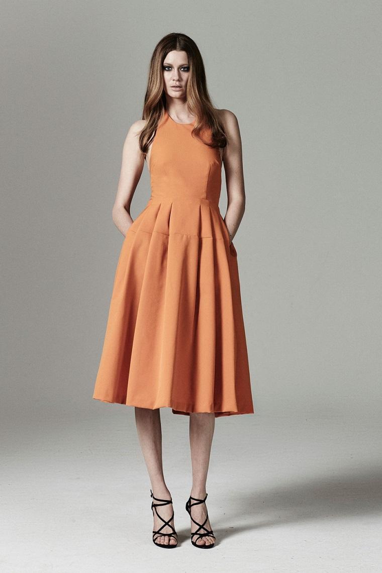 Abito schiena scoperta della fashion designer Rebecca Vallance di colore arancione con parte bassa e ruota