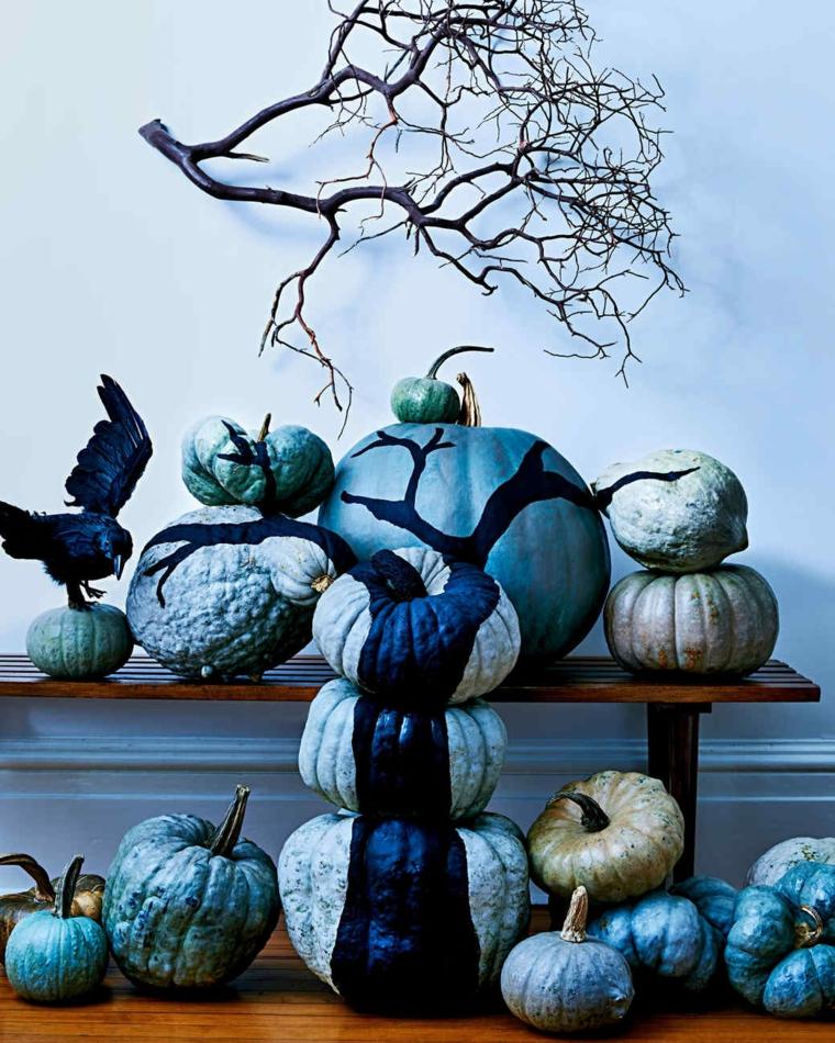 Foto zucche halloween, decorazione nella tonalità di colore blu e rami di albero sulla parete