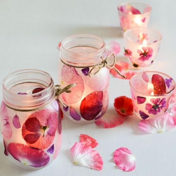 Idee artigianali con dei barattoli di vetro decorati con petali di fiori e utilizzati come portacandele