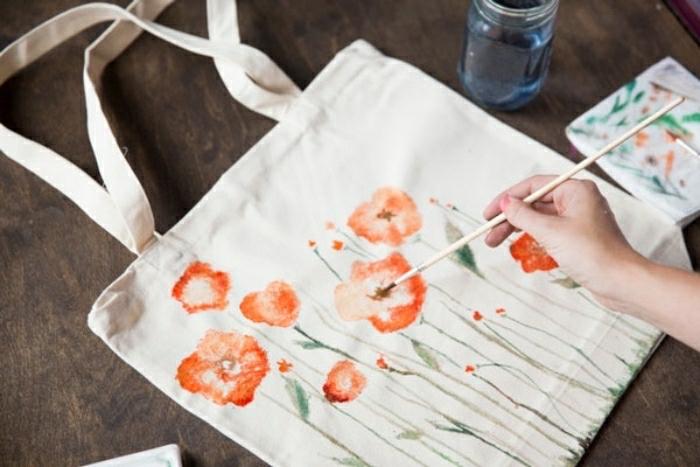 Lavori artigianali con dei colori per tessuti, borsa per la spesa decorata con dei disegni