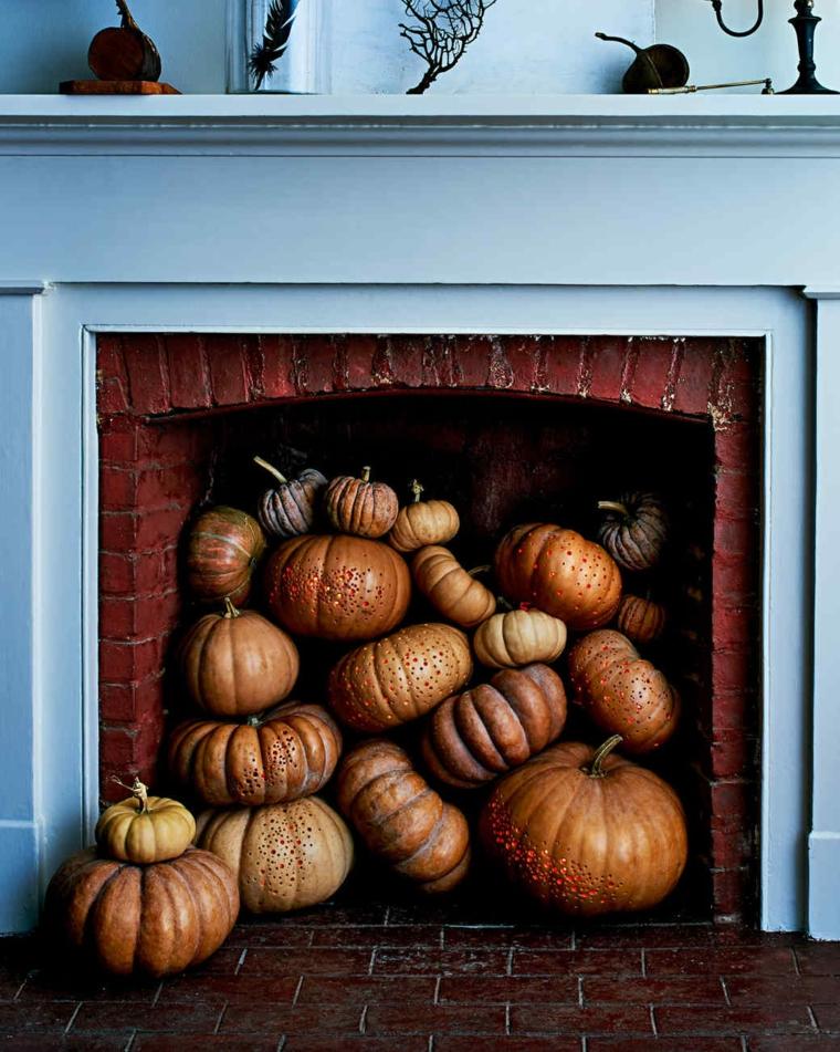 Intagliare zucca di Halloween, tante zucche dentro un camino rustico con mattoni