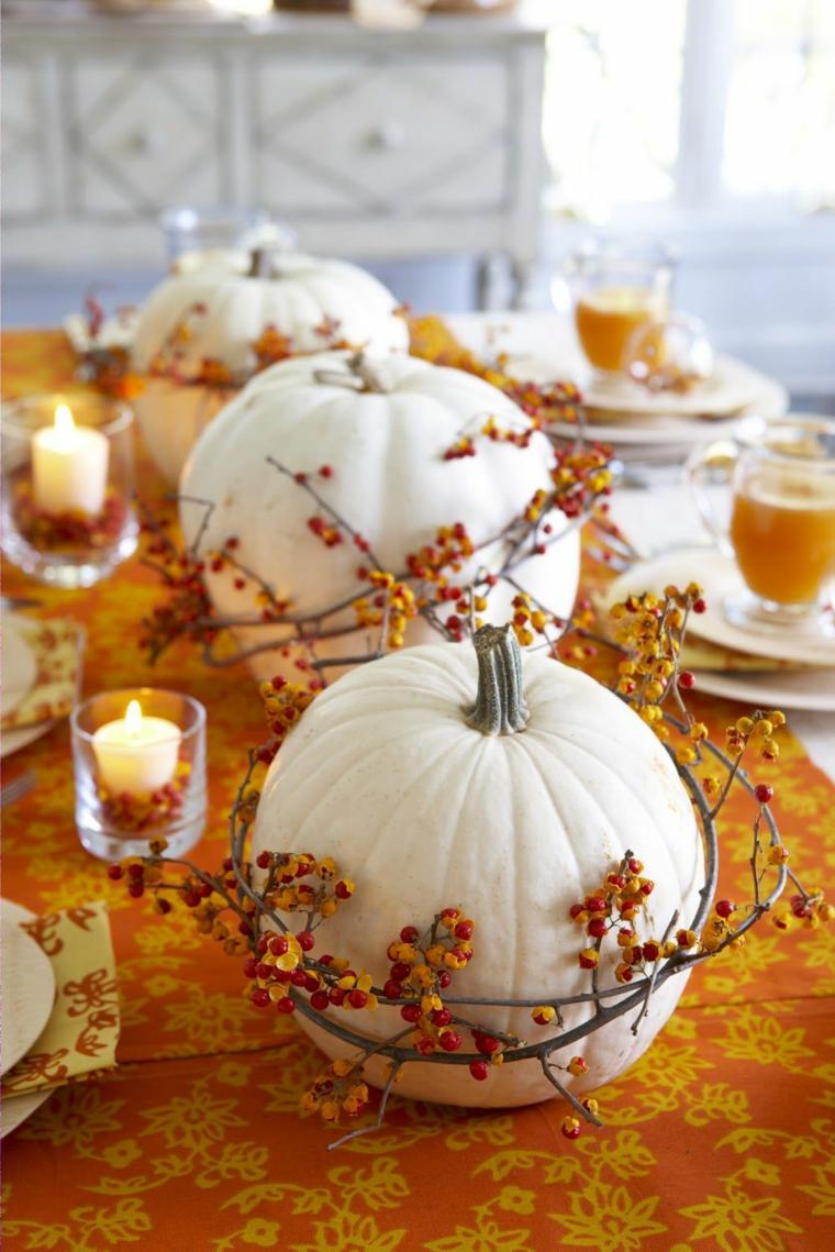 Immagini autunnali bellissime, idea per un centrotavola con zucche e rametti con bacche