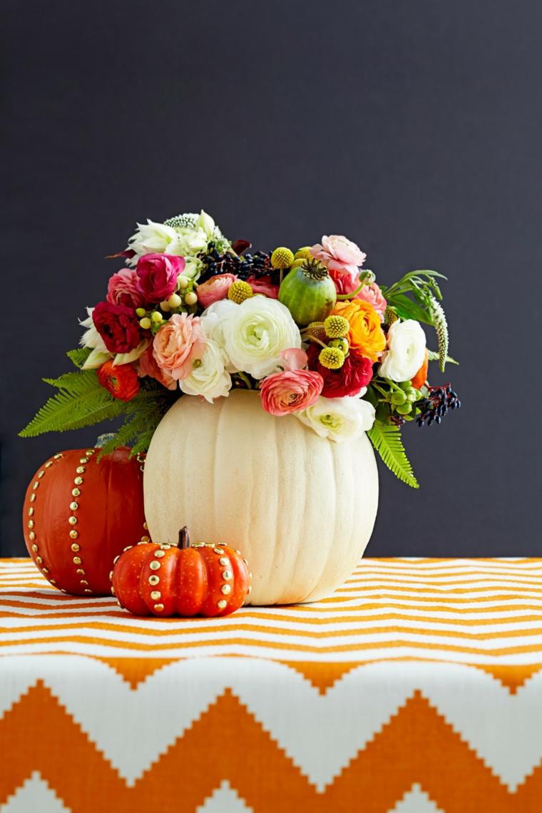 Decorazione autunnale con un vaso realizzato da una zucca, bouquet con fiori di stagione