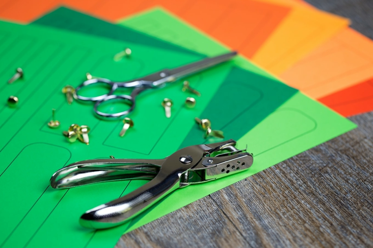 Materiale necessario come cartoncini colorati fermacampioni, forbici e perfotrice buca fogli