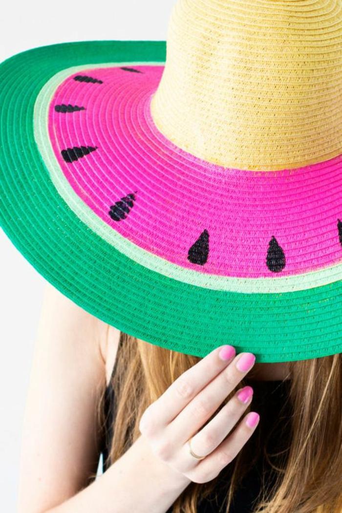 Lavori artigianali per decorare un cappello di paglia con i motivi di un'anguria