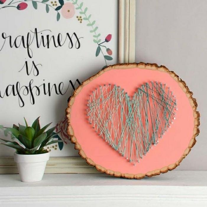 Idee lavoro creativo per decorare la casa con un pezzo di legno colorato di rosa con corda a forma di cuore