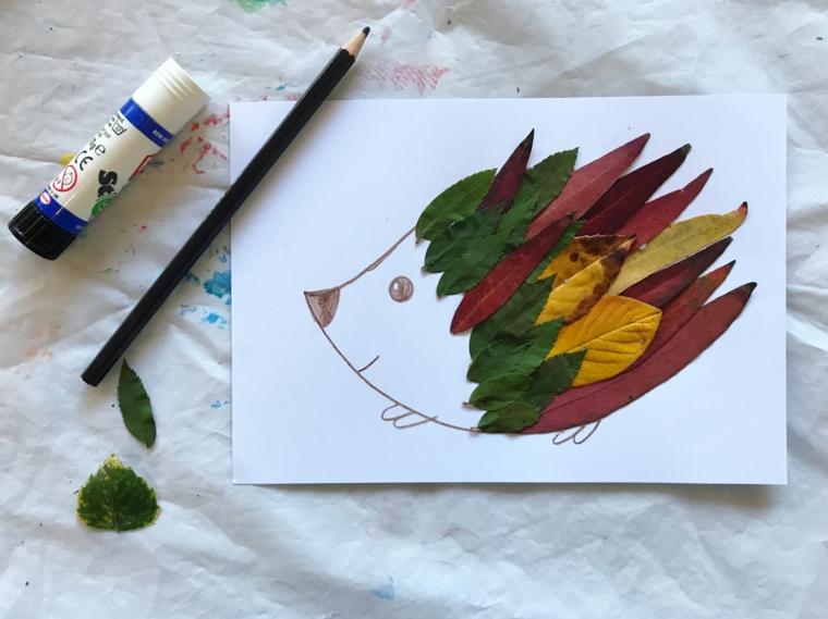 Il disegno di un bambino con un porcospino e foglie colorate autunnali