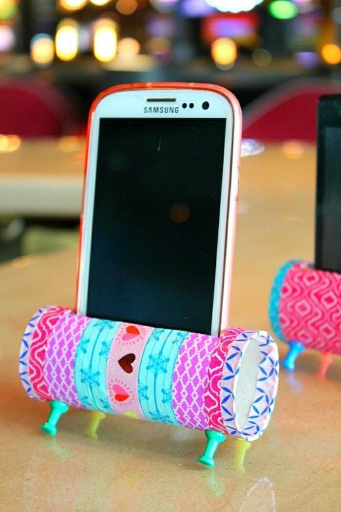 Base per un telefono realizzata da un rotolo di carta ricoperto con un pezzo di stoffa colorata