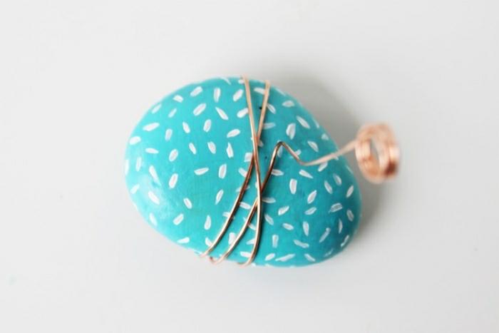 Idee artigianali con delle pietre dipinte di colore blu e filo di rame avvolto intorno