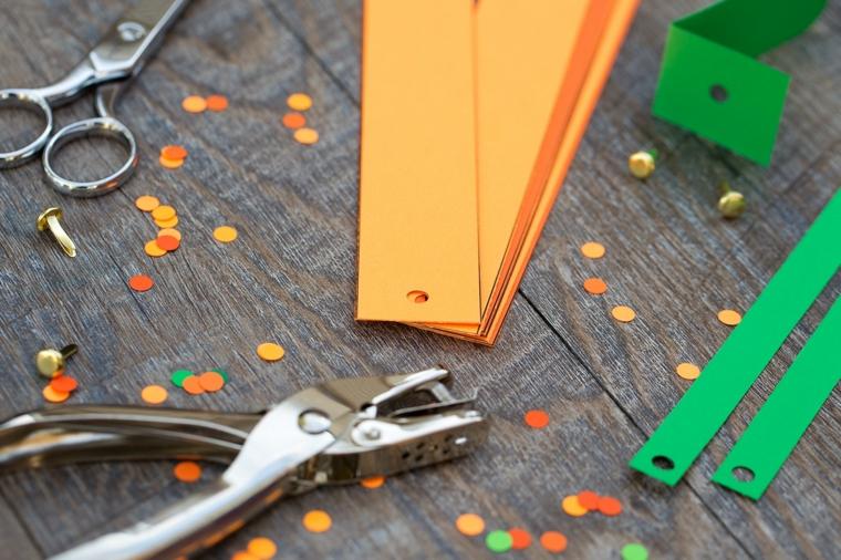 Cartoncini arancioni e verdi perforati e fermacampioni di metallo