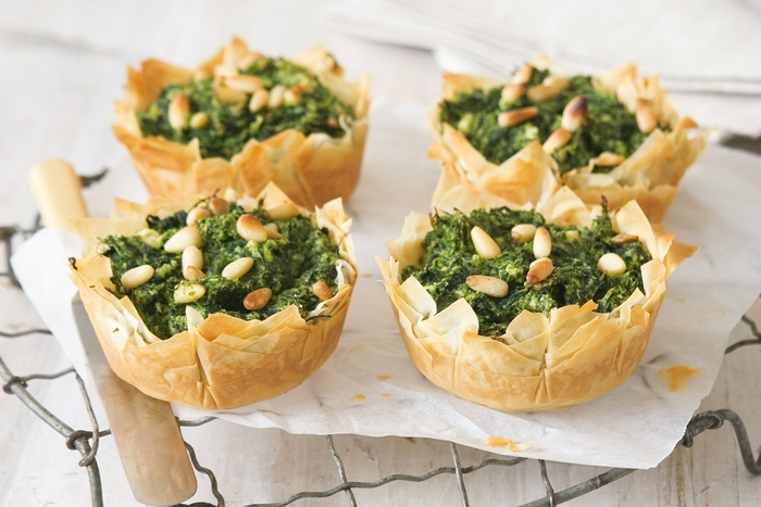Aperitivo vegetariano e dei cestini di pasta filo con spinaci e pinoli