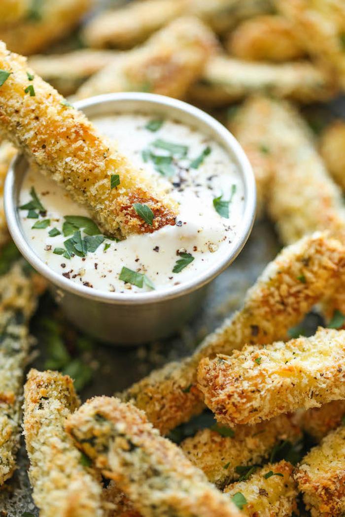 Aperitivo vegetariano e un'idea con dei bastoncini di zucchine con salsa bianca