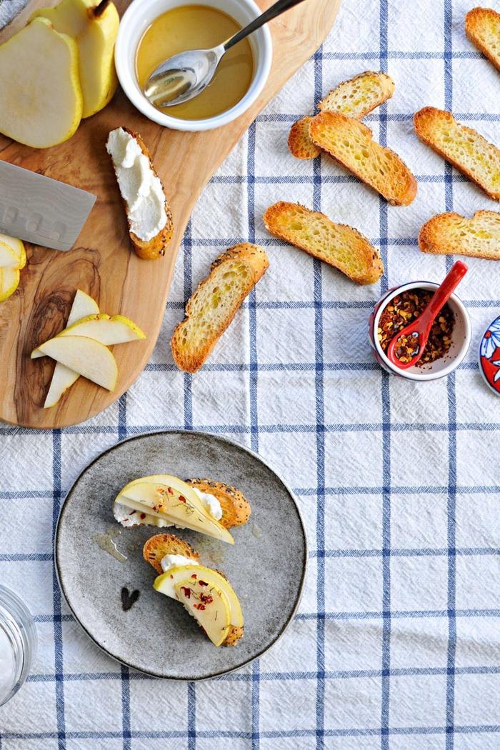 Aperitivo vegano con delle bruschette di pane con pere e formaggio ricotta spalmabile