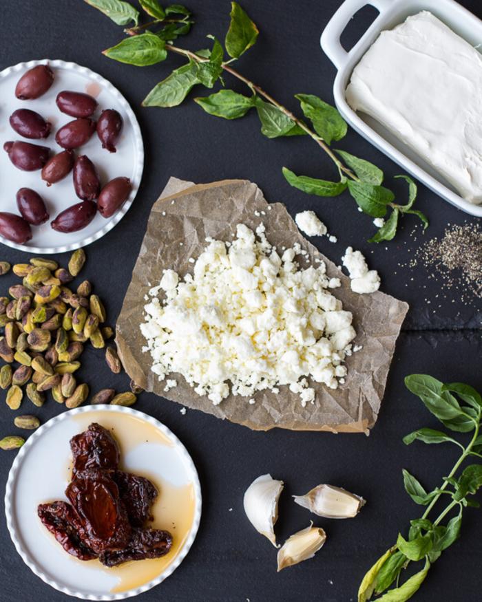 Idea con ingredienti per dei finger food vegetariani a base di olive, pistacchi e formaggio Feta