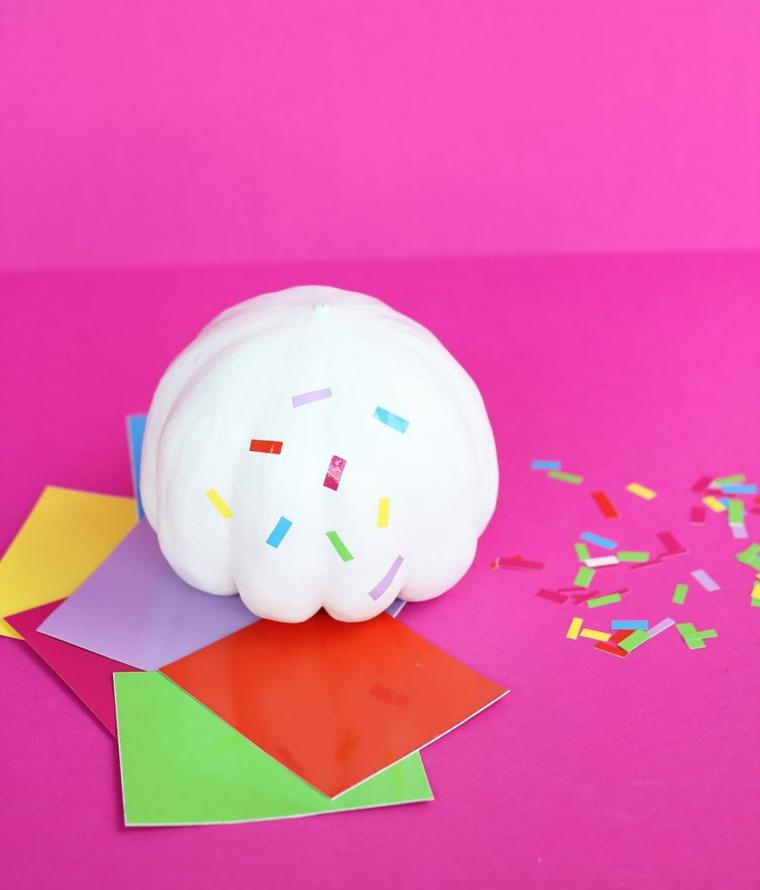 Piccola zucca di colore bianco e di plastica, pezzettini di carta adesiva colorata