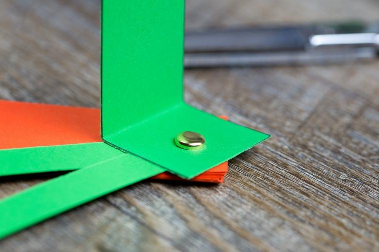 Cartoncini rettangolari di colore verde e arancione fissati con un fermacampione di metallo