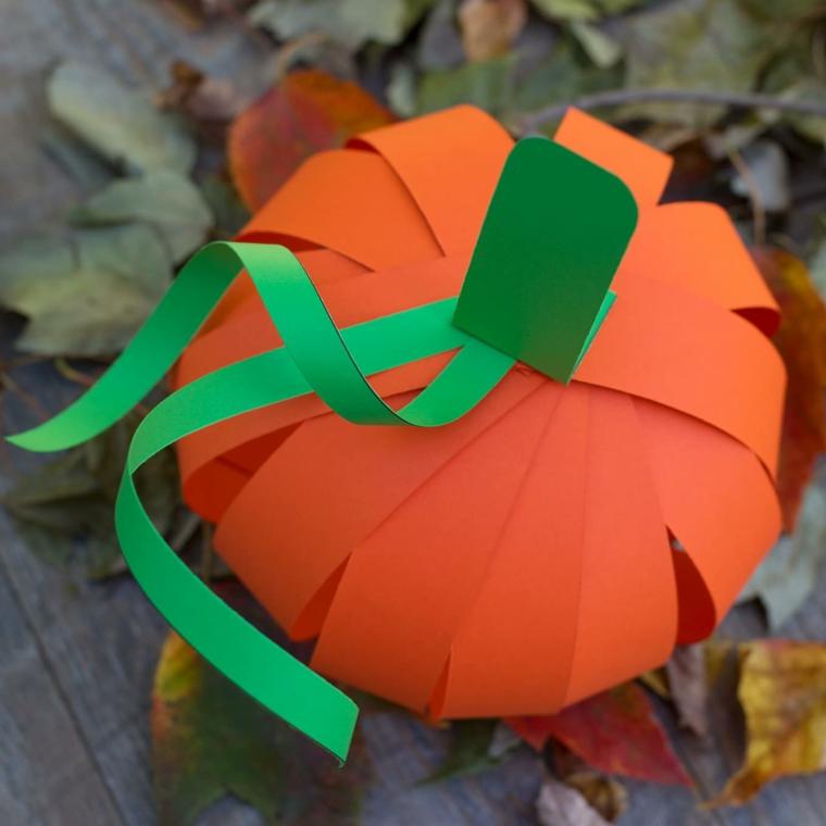Piccola zucca di carta, cartoncini arancioni e verdi fissati con un fermacampione
