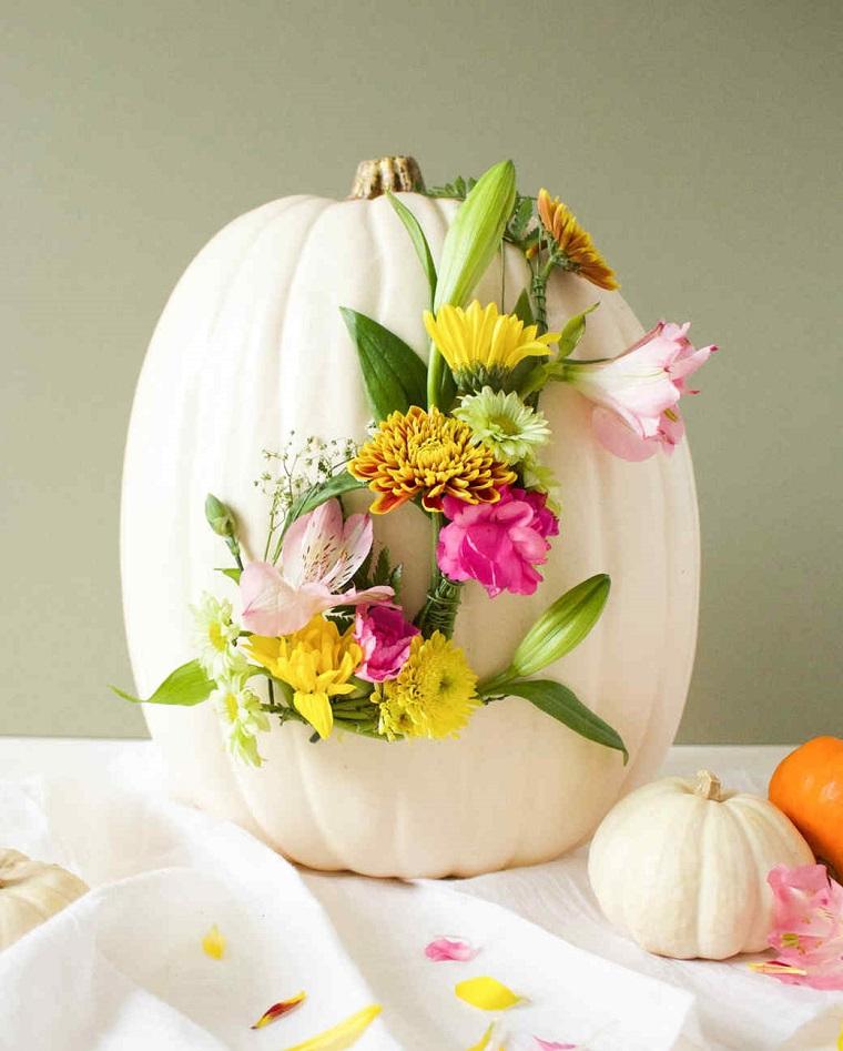 Zucche ornamentali e un'idea con una di colore bianco decorata con fiori