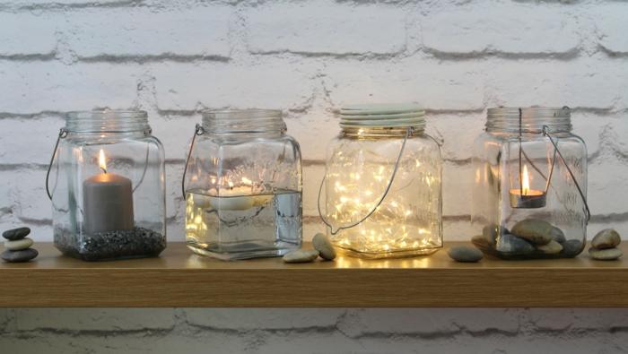 Barattoli di vetro utilizzati come delle lanterne e portacandele e fili luminosi