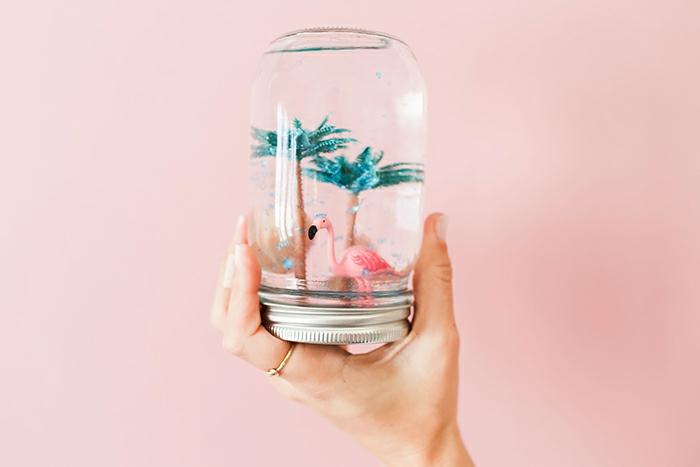 Idee lavoro creativo fai da te con un barattolo di vetro, polvere glitterata di colore blu e una figurina di fenicottero e palme
