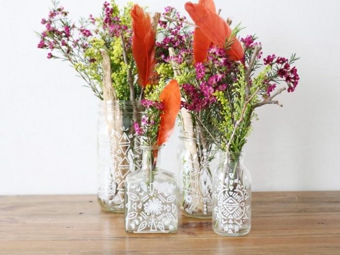 Alcune idee artigianali per decorare la casa, bottiglie di vetro e barattoli decorati come dei vasi per fiori