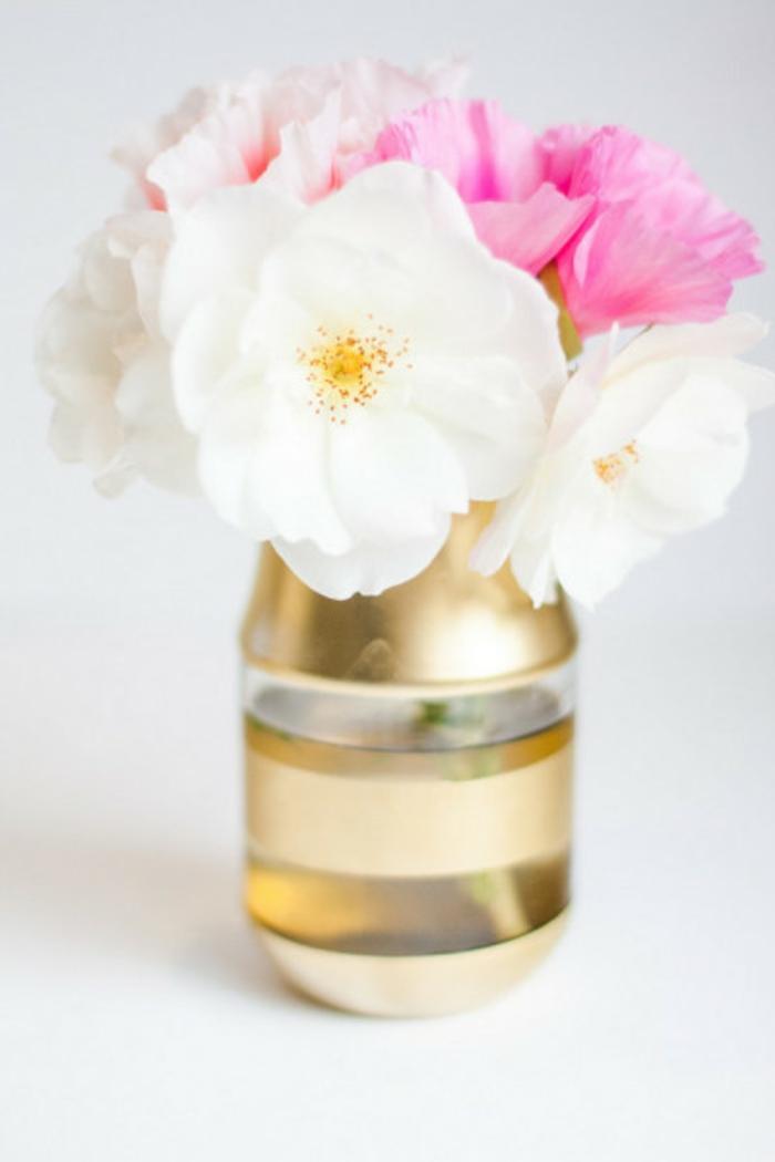 Lavori fatti a mano per decorare la casa, una bottiglia di vetro a strisce di colore oro con fiori