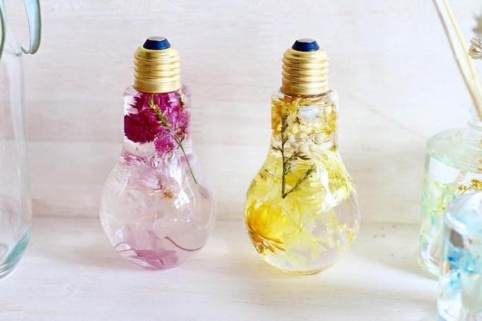 Due lampadine vecchie piene di acqua e fiori all'interno da utilizzare come decorazione