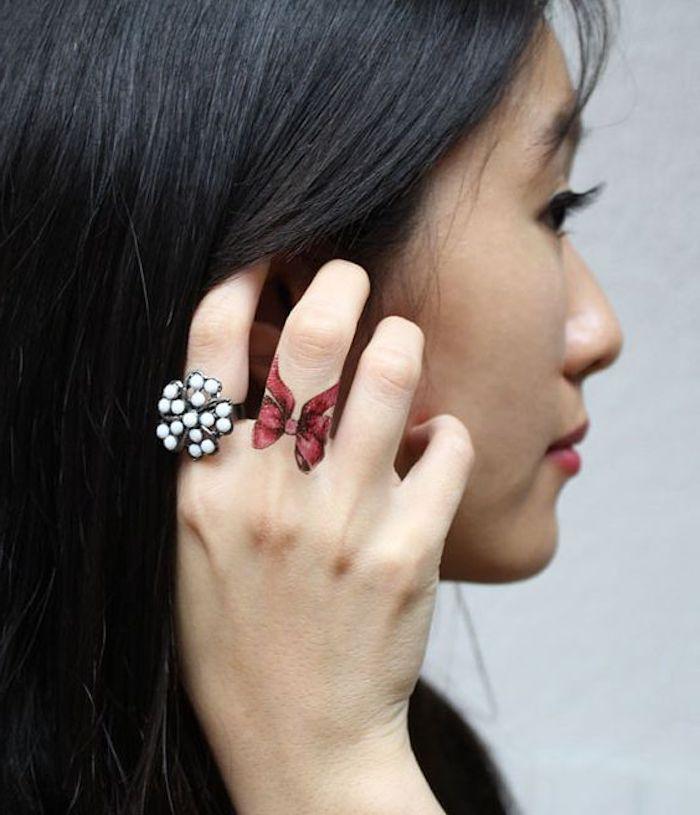Idea per dei tatuaggi sulle mani e una proposta con un fiocco rosso sul dito medio di una donna