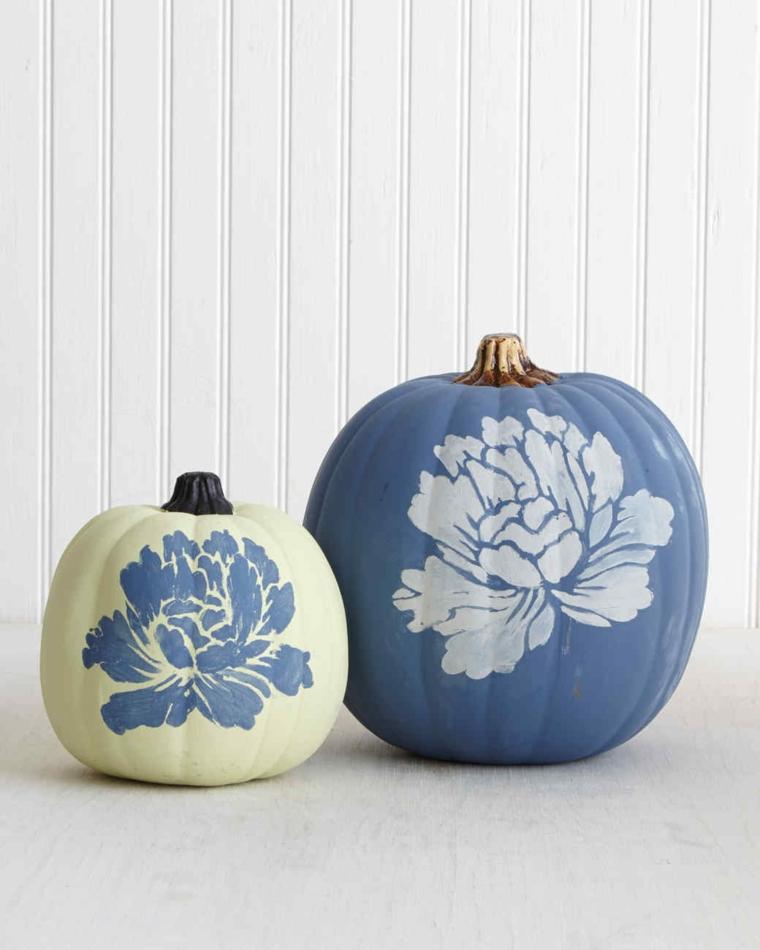 Zucche di Halloween di colore bianco e azzurro decorate con uno stencil di fiori
