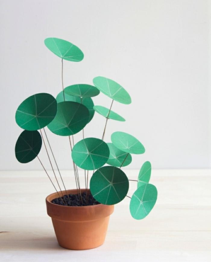 Un vaso di terracotta con una pianta dalla foglie verdi realizzata con della carta