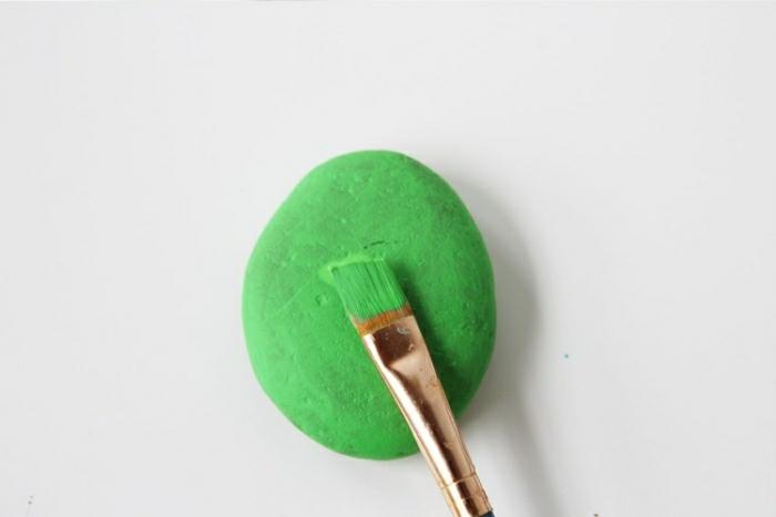 Idee lavoro artigianale con un sasso dipinto di colore verde con un pennello