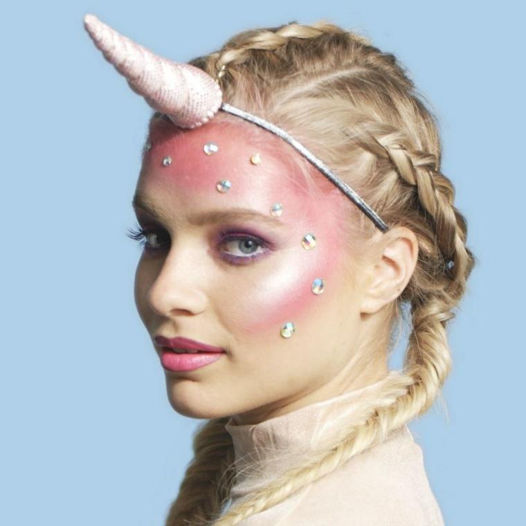 Ragazza con capelli biondi e trecce truccata come unicorno per Halloween, cerchietto e brillantini incollati sul viso