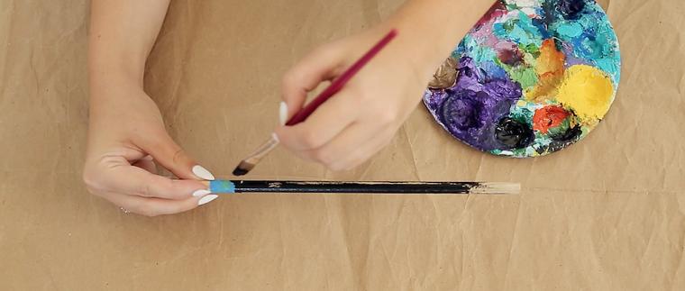 Matita di legno dipinta con diversi colori e un pennello da una ragazza