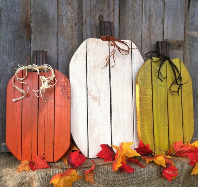 Immagini paesaggi autunnali con delle zucche finte di legno dipinte di rosso, giallo e bianco